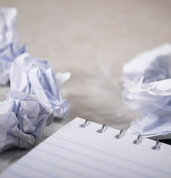 Photo of crumpled pieces of paper near a notebook.